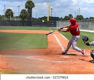Baseball player in full stride just before he hits the ball for a home run.