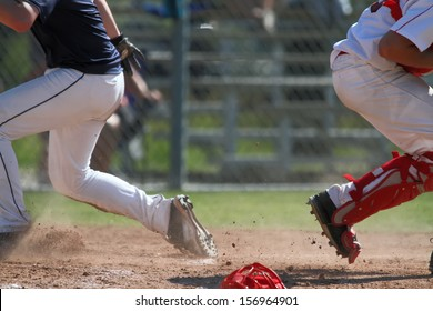 Baseball player getting to home plate with unknown results