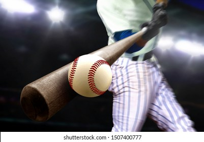 Baseball player hitting ball with bat in close up under stadium spotlights