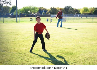 Baseball player laughing in outfield looking at camera.