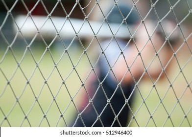 Baseball player out of focus behind baseball cage net.