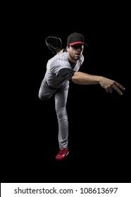 Baseball Player pitching a ball on a black background.