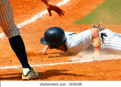 Baseball player slides by home plate with his team mate signaling safe
