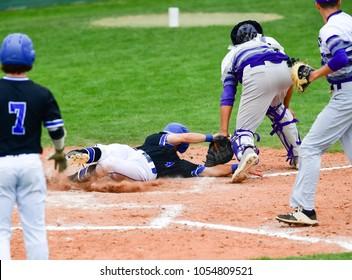 Baseball player sliding safely into base