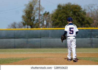 Baseball player taking the mound to pitch.