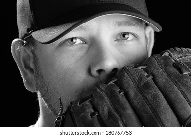 Baseball Player - This is a black and white photo of a young man wearing a baseball cap and looking out over his glove. Shot on an isolated white background and processed slightly to enhance detail.