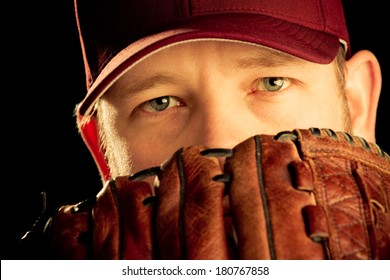 Baseball Player - This is a photo of a young man wearing a baseball cap and looking out over his glove. Shot on an black background in a warm retro color tone and processed slightly to enhance detail.