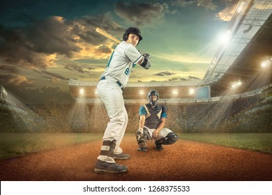Baseball players in dynamic action action under sunset sky on the stadium.