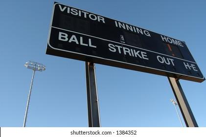Baseball scoreboard against a blue sky.