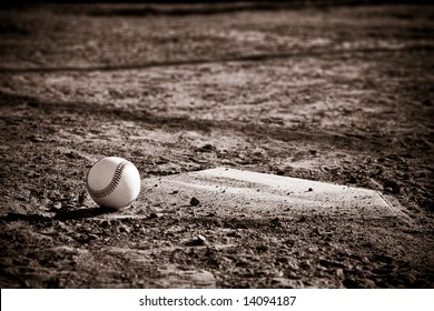 Baseball Sitting on a dirty baseball home plate with vintage sepia look and vignette