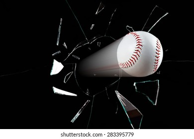 A baseball smashes through a window sending glass shards everywhere.