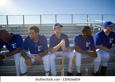 Baseball team in sitting on bench in stand during baseball game