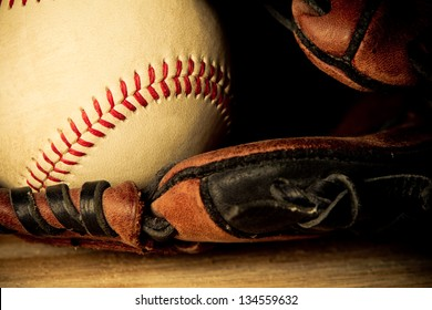 Baseball - This is a close up shot of an old baseball inside an old baseball glove on a wood background. Shot in a warm retro color tone.