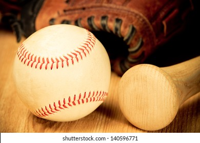 Baseball - This is a close up shot of an old baseball and wooden bad on a wood background with an old glove in the background. Shot in a warm retro color tone.