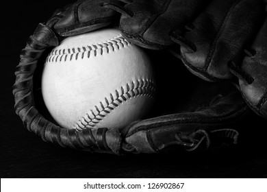 Baseball - This is a high contrast black and white photo of an old baseball inside of an old baseball glove.