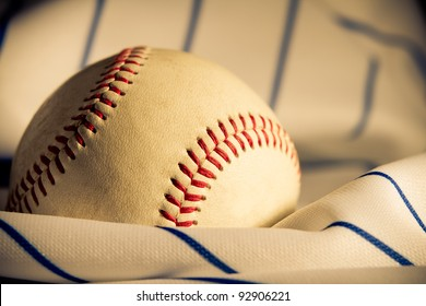 Baseball - This is a shot of an old baseball sitting on a wrinkled baseball jersey. Shot with a warm retro color tone with a shallow depth of field and vignetting.