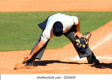 Baseball umpire dusting off dirt from home plate with a brush with his mask in his other hand