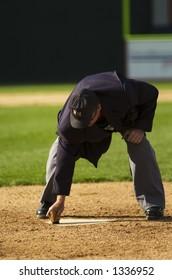 Baseball umpire sweeps home plate