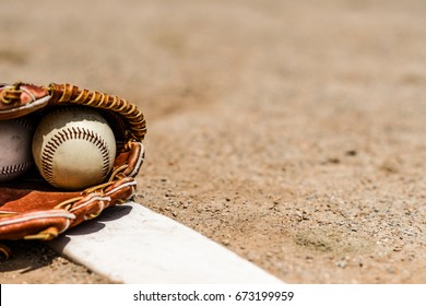 Baseballs in a glove in the dirt on a pitcher's mound