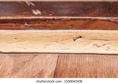The baseboard is nailed to the threshold. Home repair.