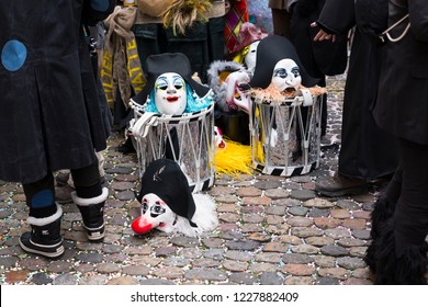 Basel carnival 2018. Andreasplatz, Basel, Switzerland - February 19th, 2018. Close-up of a pile of carnival masks and snare drums on confetti covered cobble stones