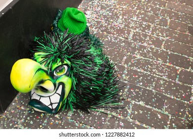 Basel carnival 2018. Gerbergasse, Basel, Switzerland - February 19th, 2018. Close-up of a single green carnival mask on confetti covered street