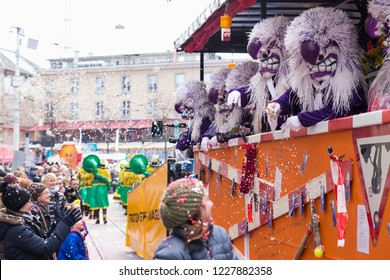 Basel carnival. Falknerstrasse, Basel, Switzerland - February 21st, 2018. Waggis clowns throwing confetti into the crowd