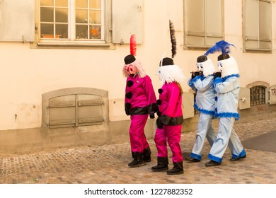 Basel carnival. Martinsgasse, Basel, Switzerland - February 21st, 2018. Group of four participants strolling in the old town