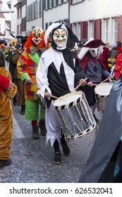Basel carnival. Nadelberg, Basel, Switzerland - March 7, 2017. One participant wearing a black and white clown costume and playing on his snare drum.