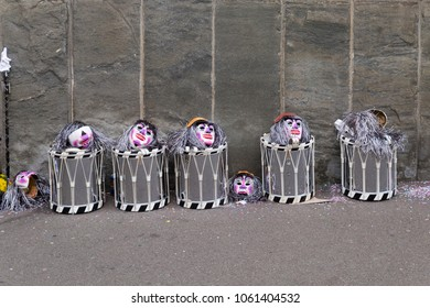 Basel carnival. Spiegelgasse, Basel, Switzerland - February 21st, 2018. Line of snare drums and masks in front of a gray wall