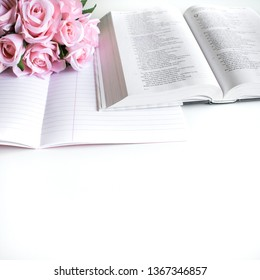 Basel Land, Switzerland - April 12, 2019: lifestyle flat lay with different accessories; flower bouquet, pink roses, open book, Bible, pen, journal, etc.