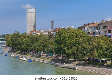 Basel, Switzerland - 6 August, 2014: view on the Rhine river with the Novartis building in the background. Basel is a Swiss city, located where the Swiss, French and German borders meet.