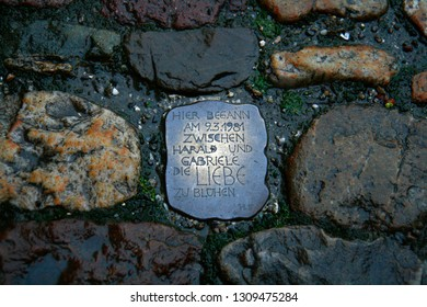 """Basel, Switzerland - February 24, 2007: a piece of metal engraved in the pavement in the style of a stumbling stone with the writing """"here the love between Gabriele and Harald began to blossom (date)"""""""
