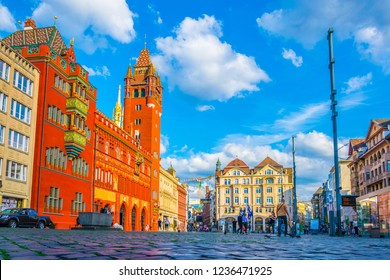 BASEL, SWITZERLAND, JULY 14, 2017: People are strolling on the Marktplatz in front of the red town hall in Basel, Switzerland