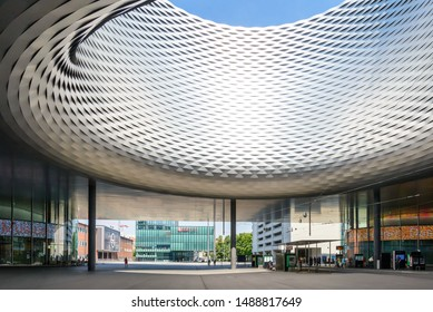 Basel, Switzerland - July 2018: View of meeting plaza and tram stop at Basel Exhibition Centre under circular hole roof and woven pattern aluminium panel facade designed by Herzog & de Meuron.