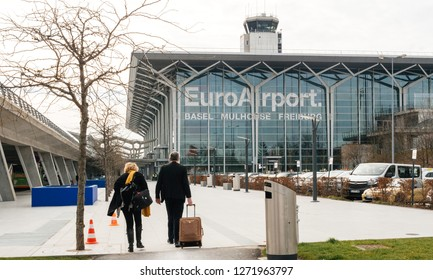 BASEL, SWITZERLAND - MAR 22, 2018: Commuters couple walking toward EuroAirport Basel Mulhouse Freiburg glass facade - wide angle view