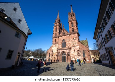Basel, Switzerland - March 10, 2019: Basel Minster with people in front of it. The Basel Minster is one of the main landmarks and tourist attractions of the Swiss city of Basel.