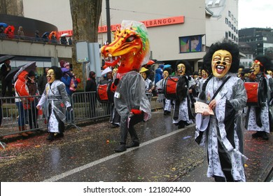 Basel, Switzerland - March 6, 2017: Participants of different Cliques marching along the street during famous Carnival of Basel (Basler Fasnacht, Cortège) in traditional wooden masks (Larve).
