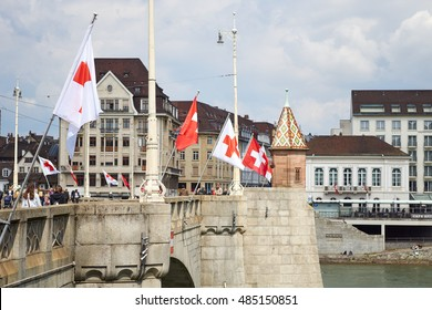 BASEL, SWITZERLAND - MAY 2016: Swiss and Red Cross flags flying on the Mittlere Bruecke over the Rhine river, with pedestrians.