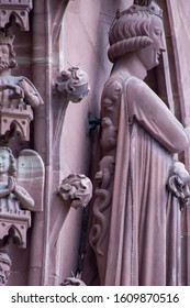 Basel / Switzerland - May 31 2019: Basel Minster or Munster Cathedral West Facade with a Side View of the Seducer or the Prince of the World