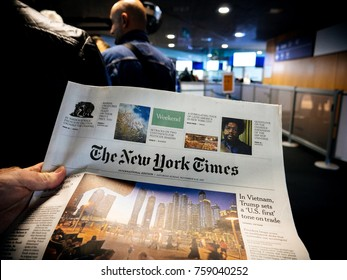 BASEL, SWITZERLAND - NOV 11, 2017: Businessman in POV reading the New Yourk Times newspaper in the waiting queue lounge at EuroAirport Basel Mulhouse Freiburg