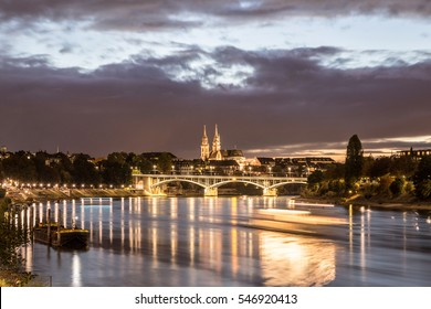 Basel, Switzerland - October 20, 2016: Night view of the Rhine River with the illuminated Basel Minster