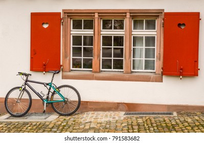 Basel, Switzerland - traditional window with heart shapes on red window shutters, with a bike under the window