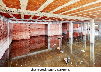 The basement of a building under construction is filled with dirty flood water