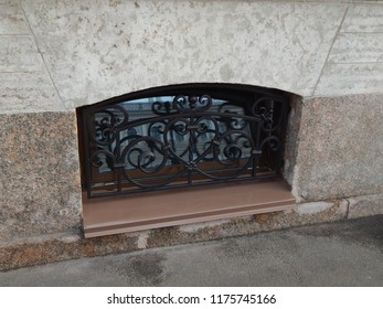 The basement window with a metal patterned lattice and the reflection of the house in front of it