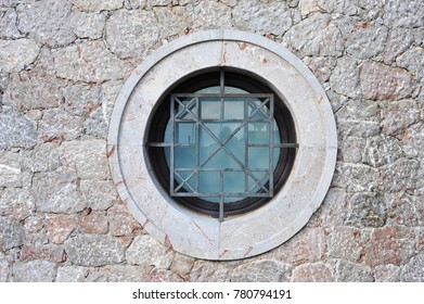 Basement Window in a new built Wall of colored cuboid natural Rocks