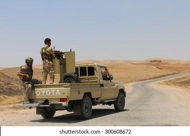 BASHIK FRONTLINE, KURDISTAN, IRAQ - 2015 JULY 25  - Two unidentified kurdish (peshmerga) fighters in back of truck at BASHIK (bashik) base 25km from ISIS controlled Mosul.