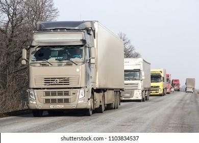 Bashkortostan, Russia - March 21, 2013: Line of dirty semi-trailer trucks at the interurban freeway.