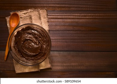 Basic brownie, chocolate cake or cookie dough in glass bowl with wooden spoon on the side, photographed overhead on dark wood with natural light (Selective Focus, Focus on the top of the dough)