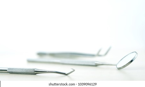 Basic dentist tools isolated on white: dentist mirror, forceps curved, explorer curved, dental explorer angular and explorer curved with chip, right. Dental Hygiene and Health conceptual image